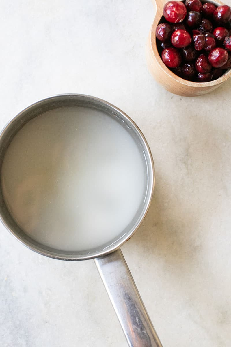 Sauce pan with sugar and water and a cup of fresh cranberries a wooden measuring cup.