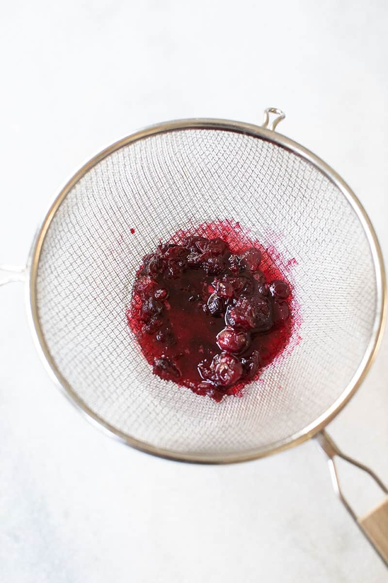 Cranberry syrup in a sieve.