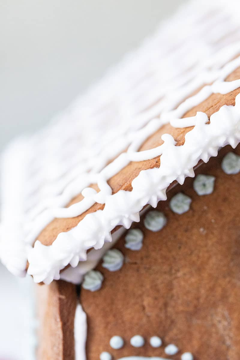 Royal icing details with a Wilton star tip on a gingerbread house.
