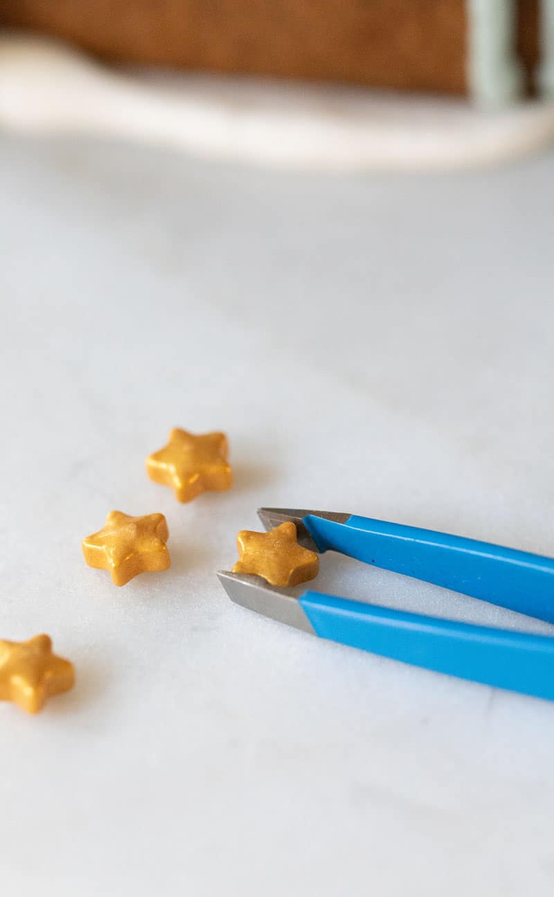 using tweezers to pick up tiny gold stars to decorate a gingerbread house.