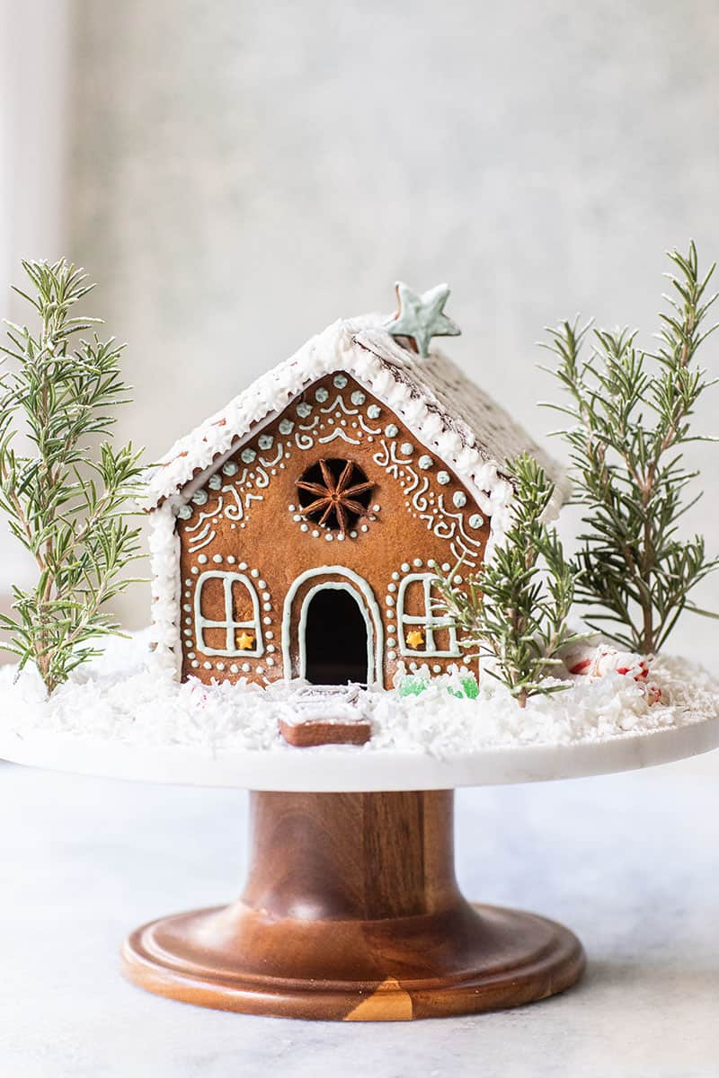 A charming gingerbread house with snowy frosting, rosemary trees and royal icing details.