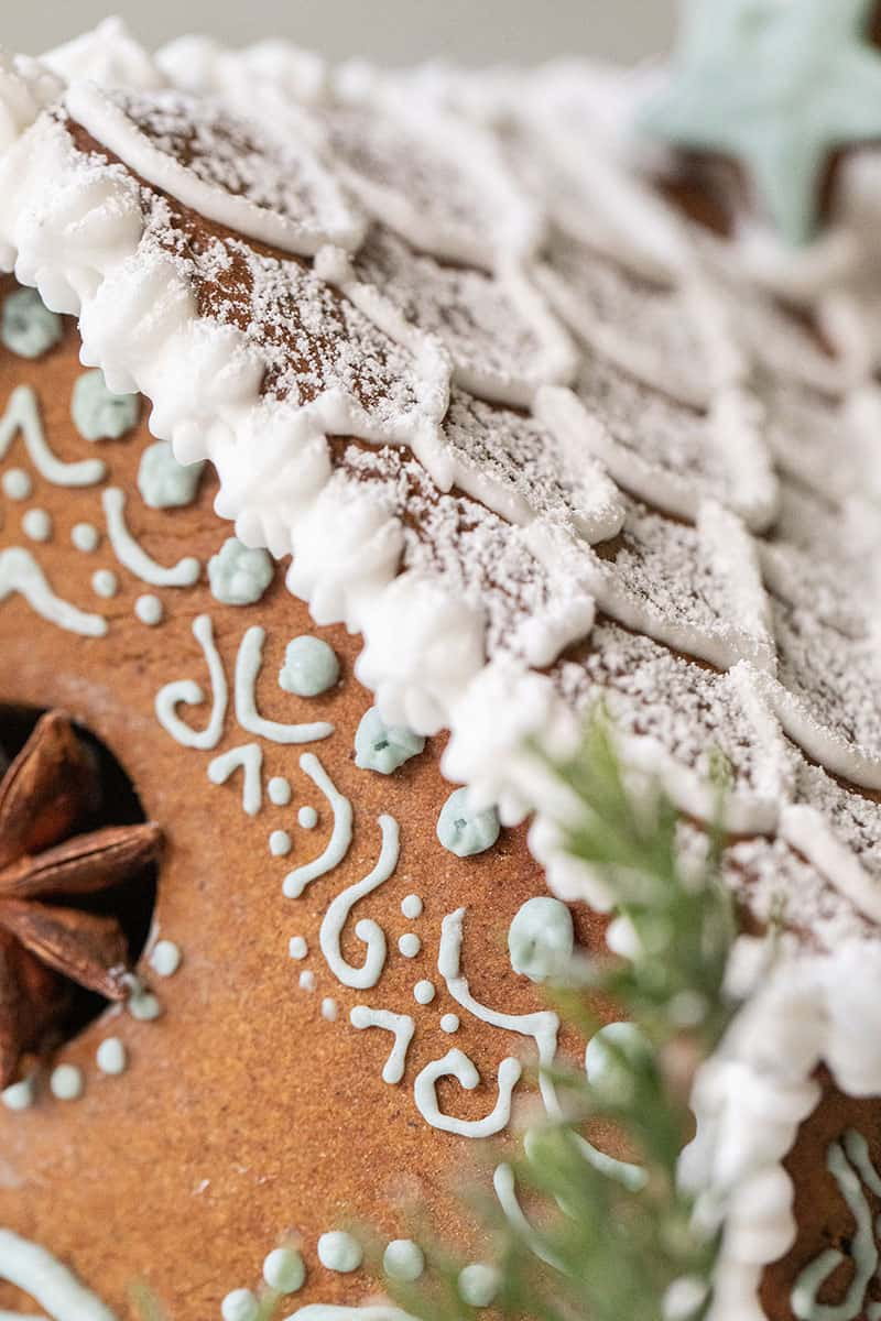 Gingerbread house with royal icing, powdered sugar and decorations.