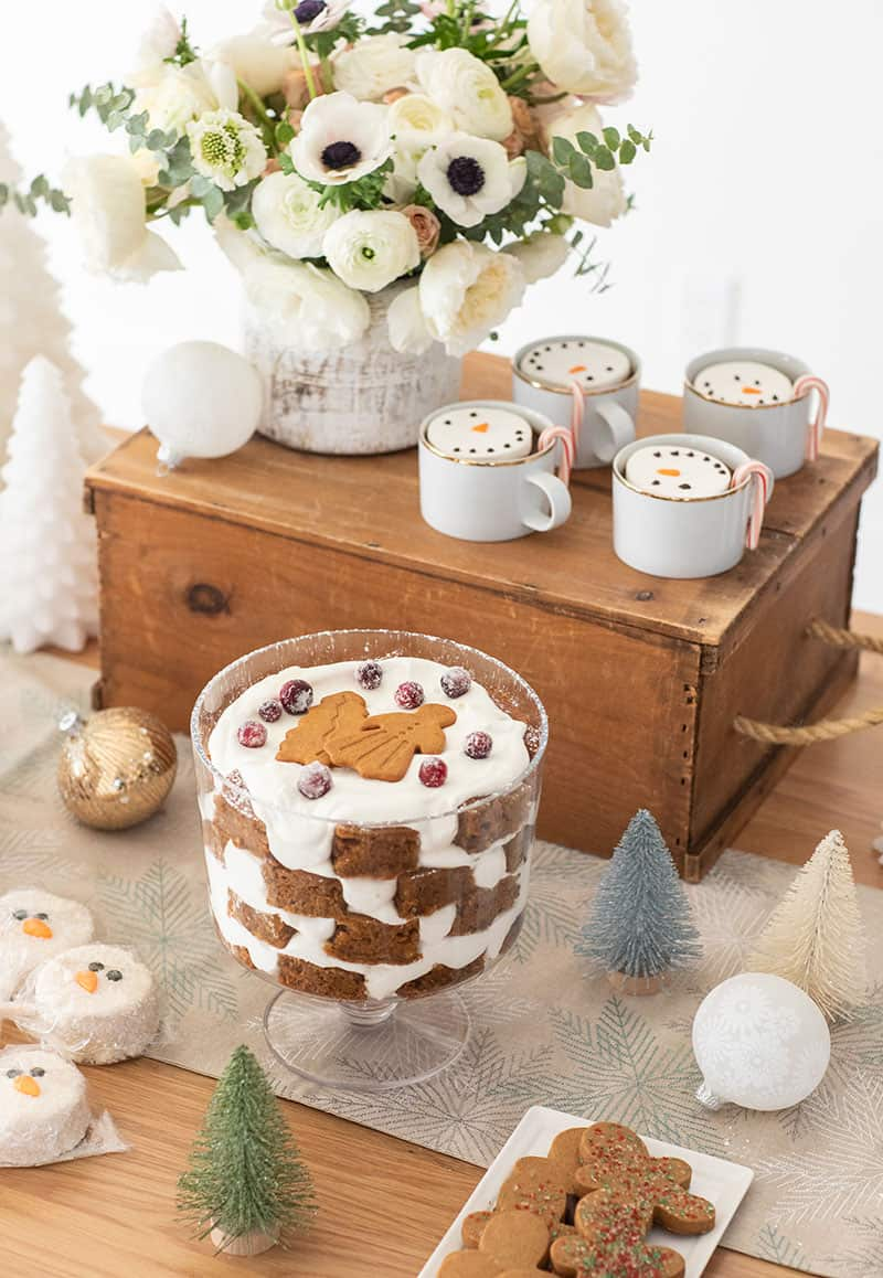 Christmas dessert table with white flowers, gold cups with marshmallow snowmen, gingerbread trifle.