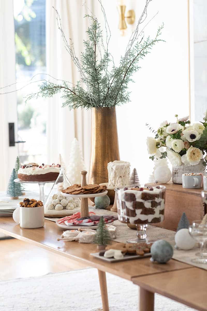 Christmas dessert table with cakes, cookies, flowers and brass vase with branches.