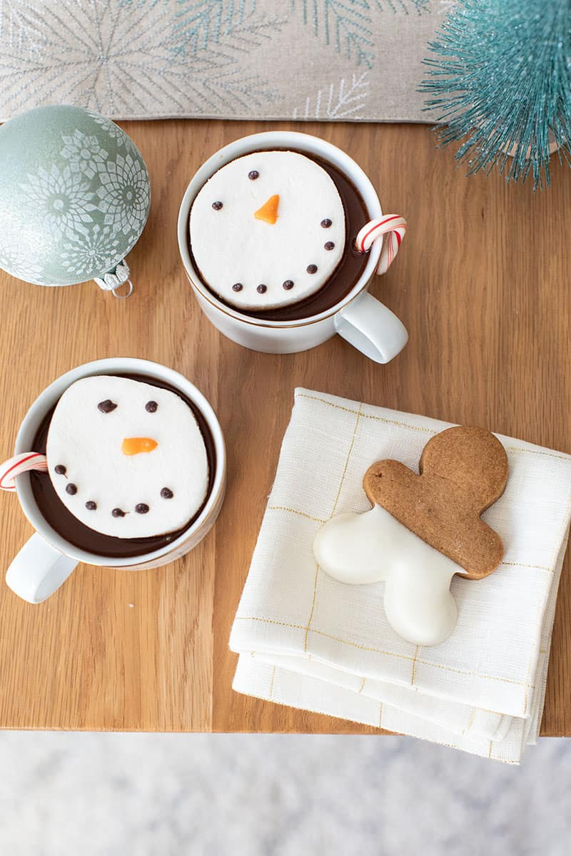 Table top with hot chocolate and snowmen marshmallows, a gingerbread cookie on a white and gold napkin and a sage ornament