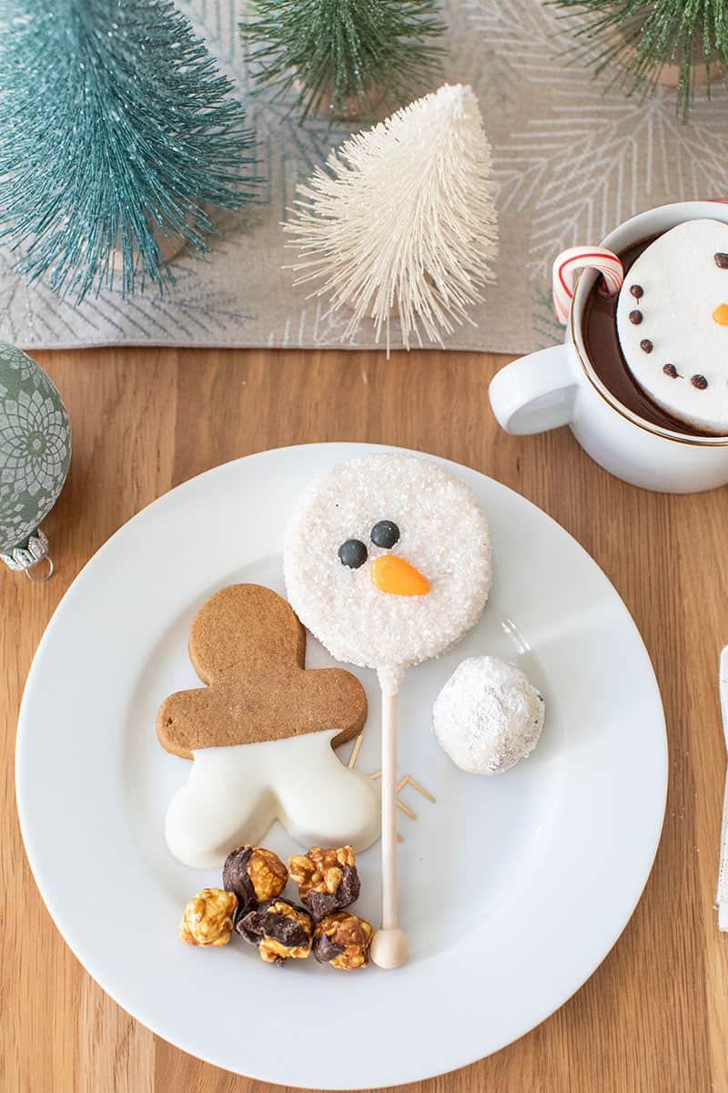 Holiday desserts on a gold and white plate. Gingerbread cookie, snowman, snowman cookie and popcorn.