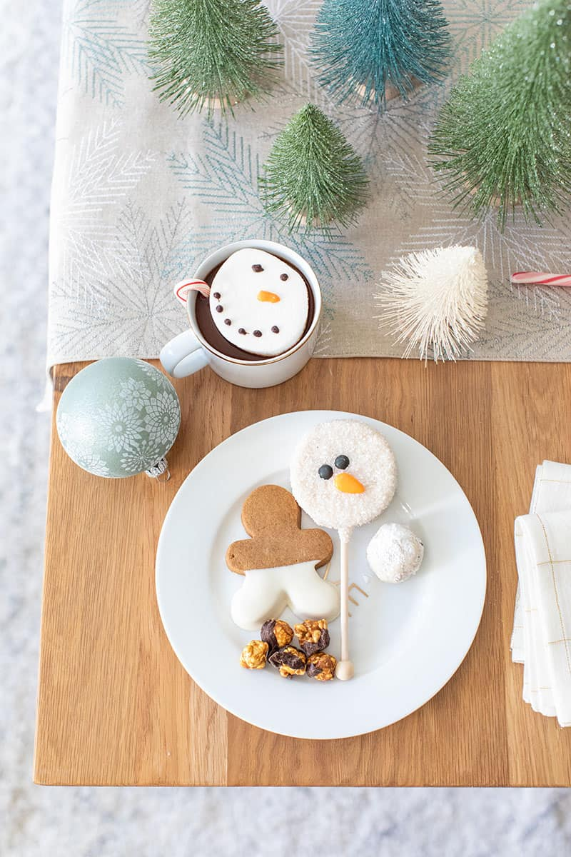 Holiday desserts on a gold and white plate with a snowman cake pop and gingerbread cookie.