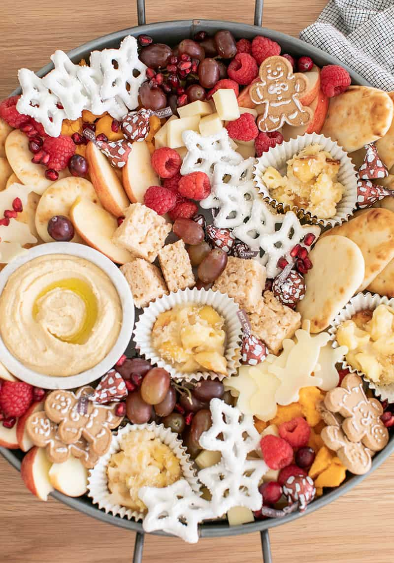 A round tray filled with Christmas Appetizers for Kids. Hummus, cheese, berries, cookies.