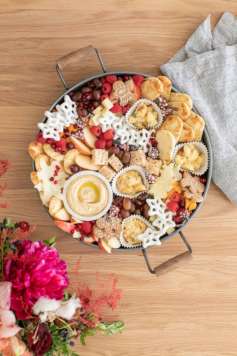 A round tray filled with mini desserts, fruit, hummus and more for a Christmas appetizer platter for kids.