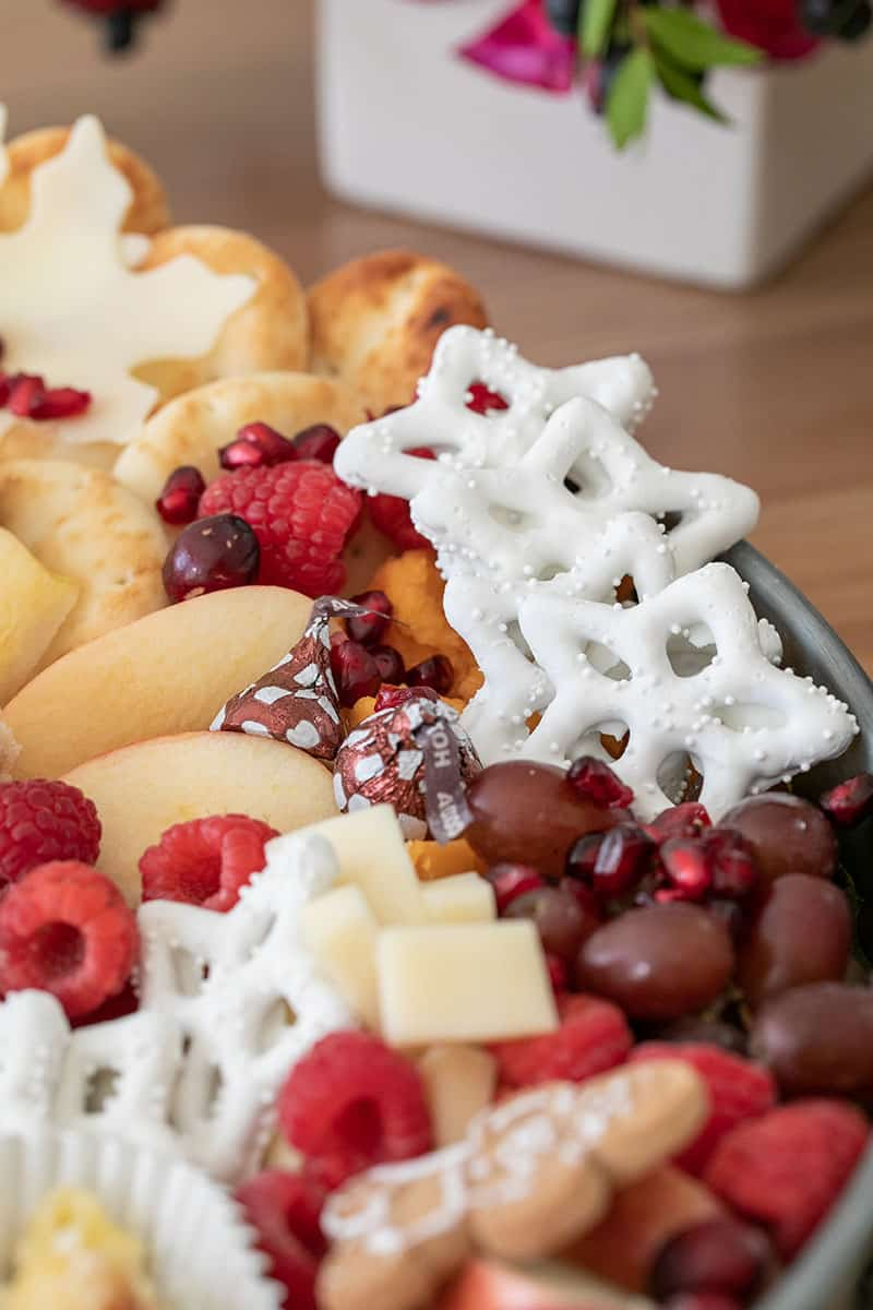 Yogurt covered pretzels, grapes, cheese, apples and pita bread on a round tray.