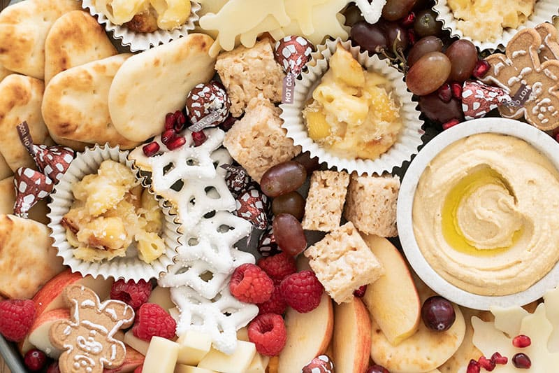 Pita bread, hummus, yogurt covered pretzels, berries, grapes all on a kids appetizer platter.