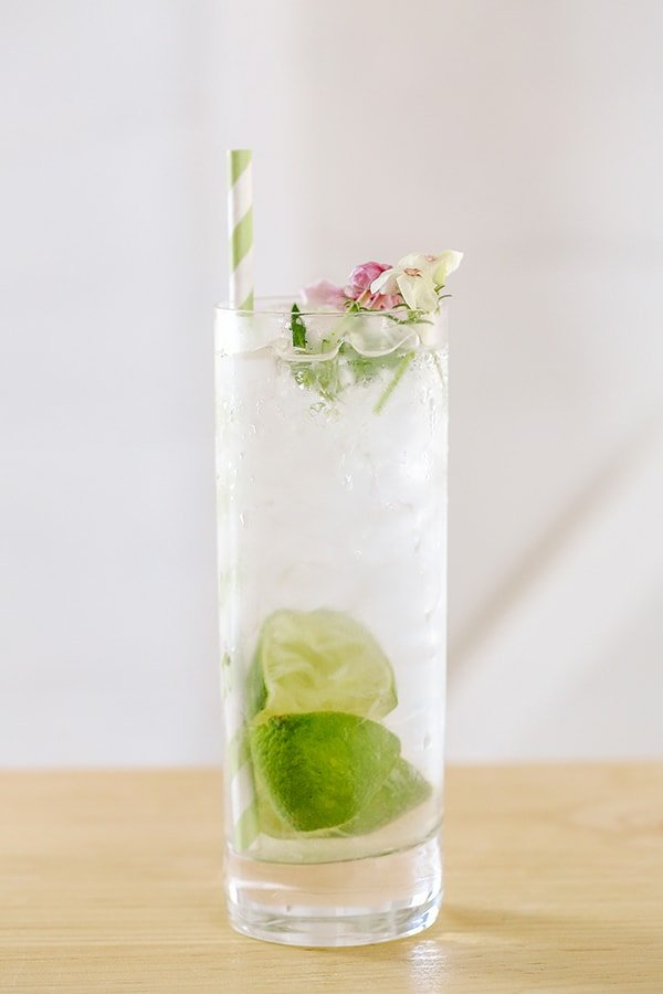 A classic gin and tonic in a highball glass with edible flowers, limes and a green paper straw.