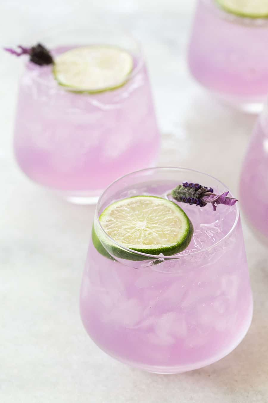 Purple, lavender gin and tonic with a lime slice and fresh lavender.