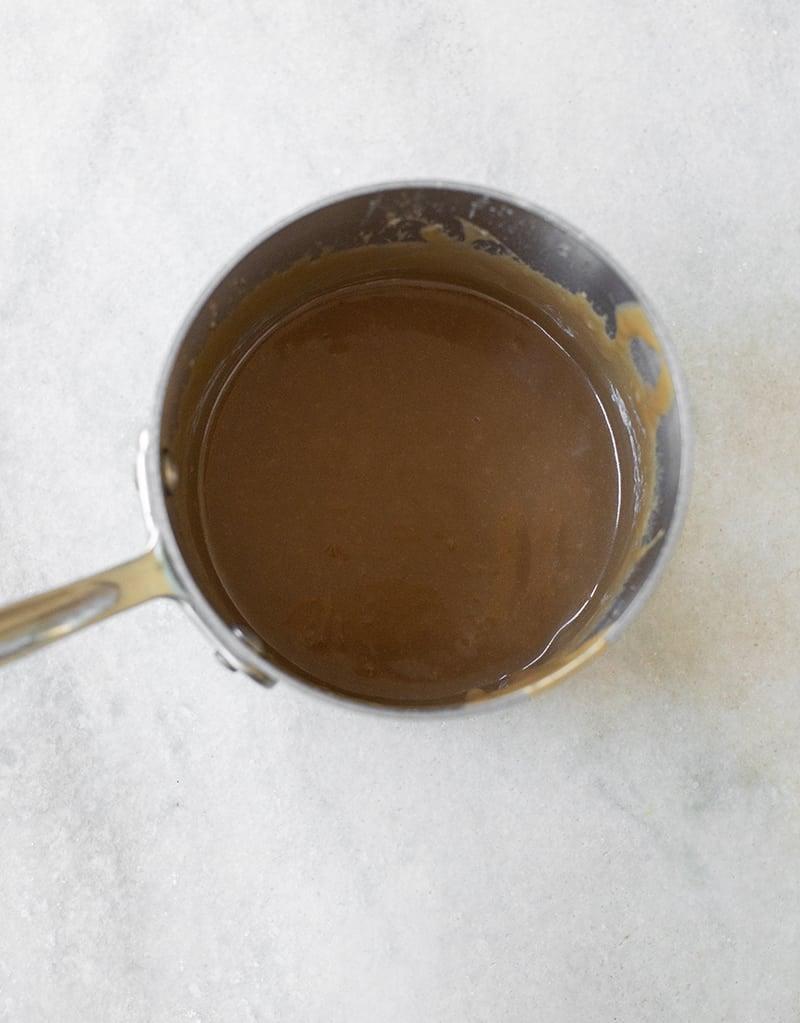 Homemade caramel sauce in a saucepan on a marble table.