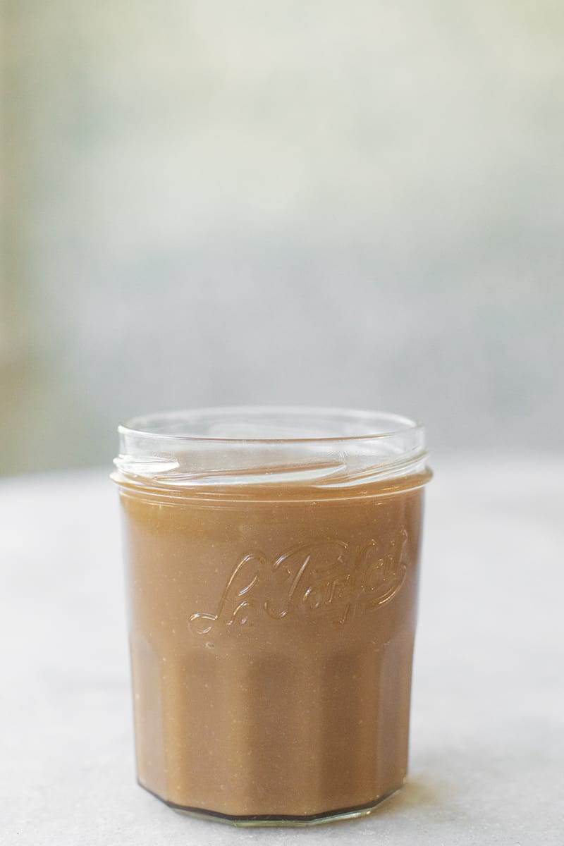 Jar of caramel sauce on a marble table.