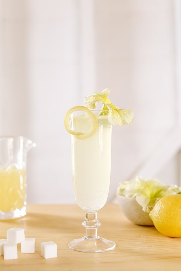 How to Make a French 75 cocktail with a lemon rind and a beautiful yellow flower.