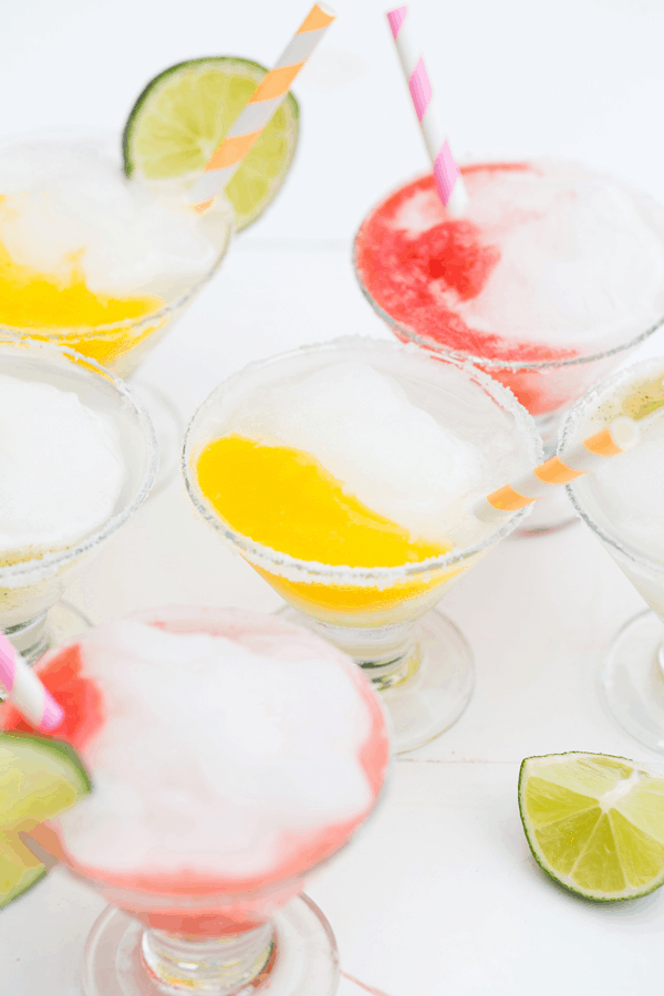 Mini frozen margaritas with paper straws.