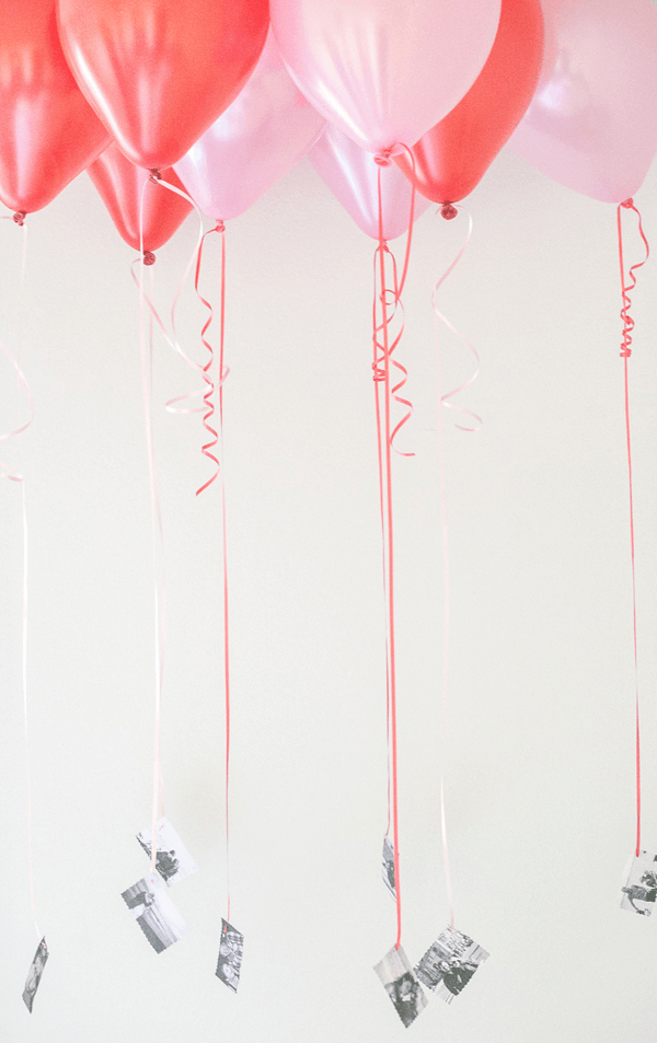 Pink and red balloons with black and white photos attached to the bottom.
