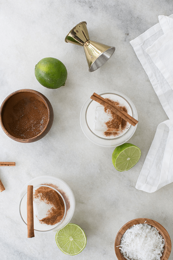 Two coconut margarita recipes with cinnamon and limes on a marble table.