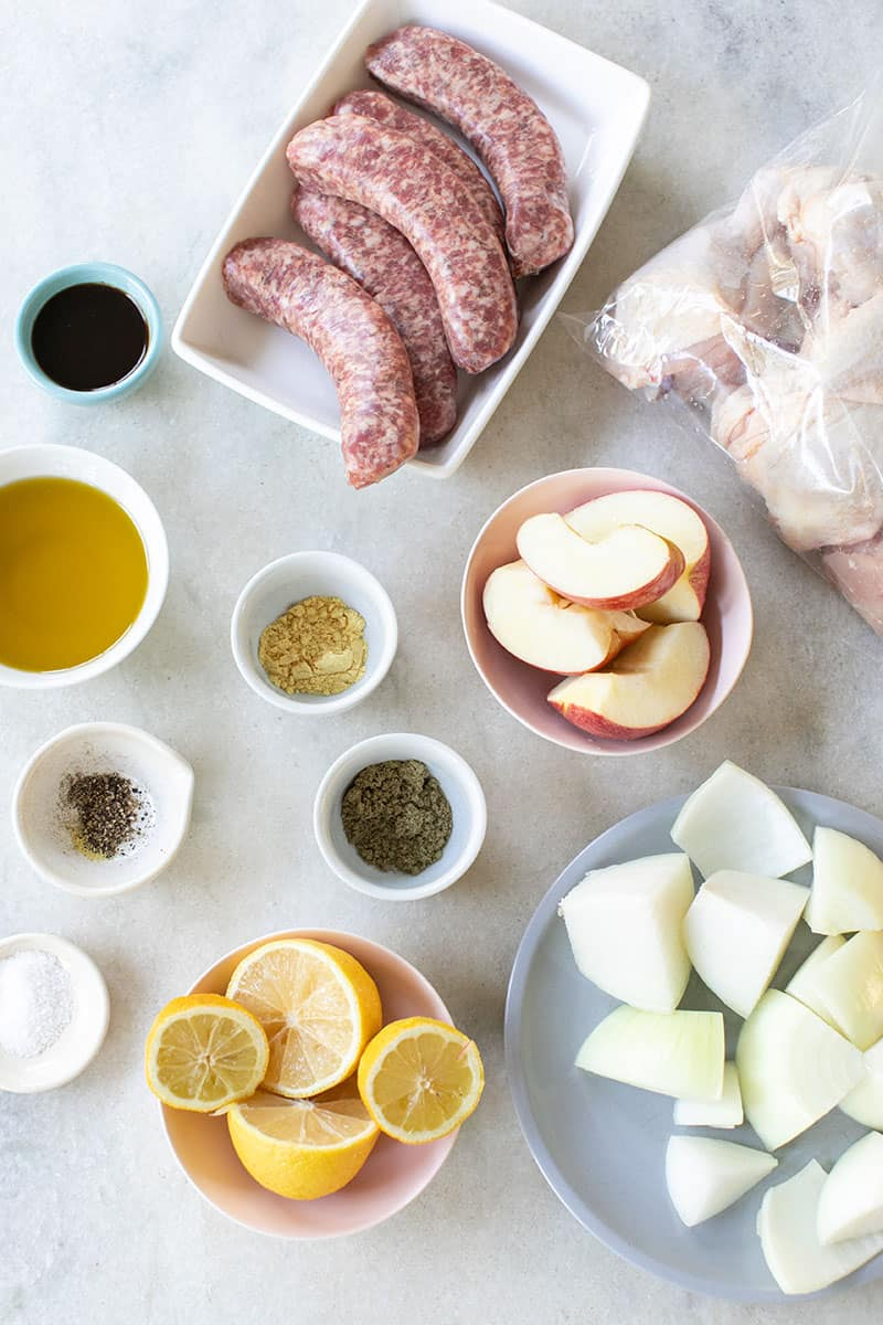 Ingredients on a marble table to make a One-Pan Chicken and Sausage Bake.