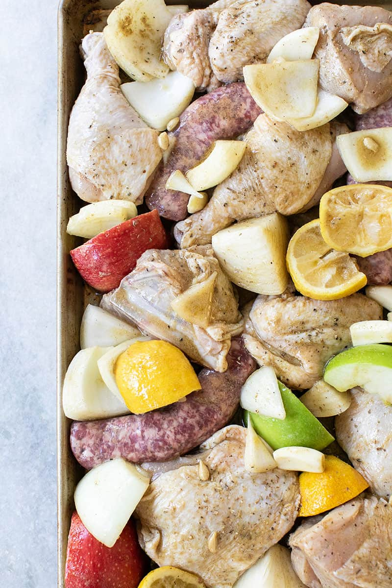 Raw chicken, sausage, apples, lemons, onions on a gold sheet pan before baking.