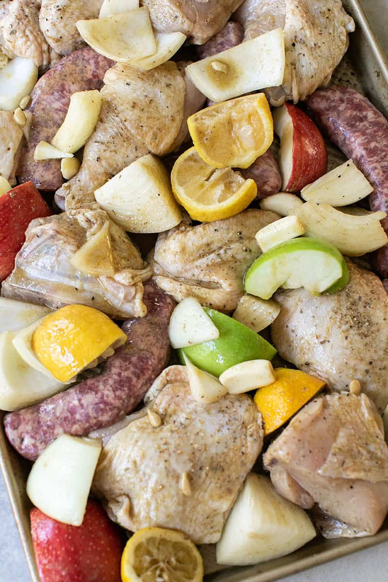 Garlic, chicken , lemons, apples, sausages on a sheet pan before baking for an easy dinner.