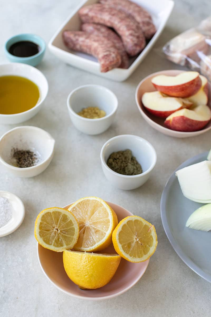 Spices, lemons, apples, onions, sausage, chicken and olive oil on a marble table to make a one-pan chicken and sausage bake.