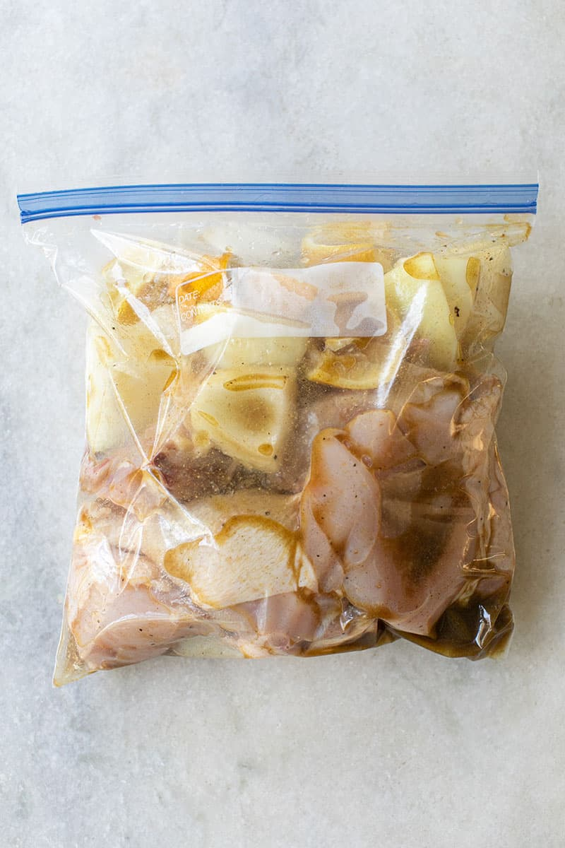 Chicken, onions, apples, sausage in a plastic bag with a marinate sauce.