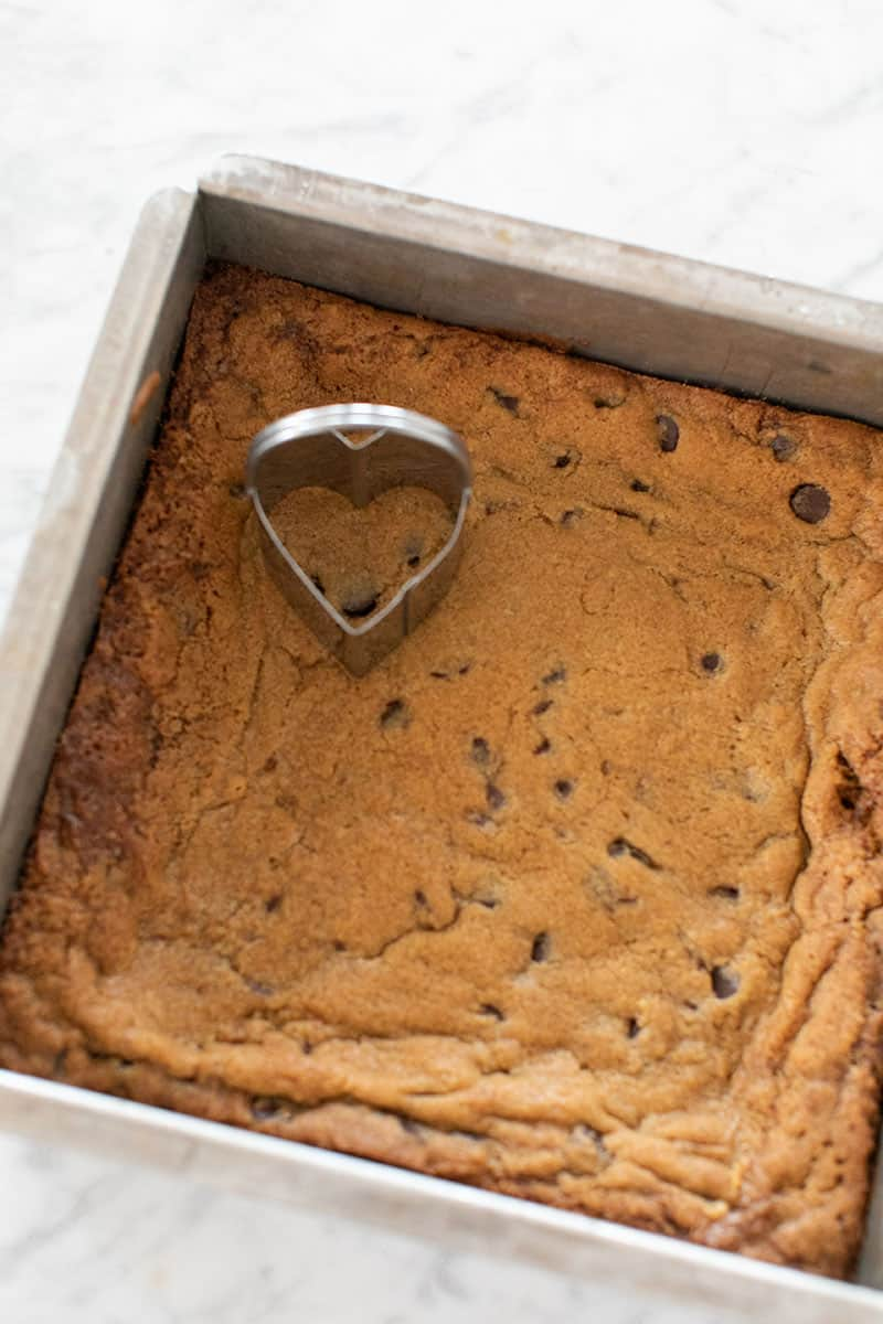 Blondies in a pan with a heart shaped cookie cutter.
