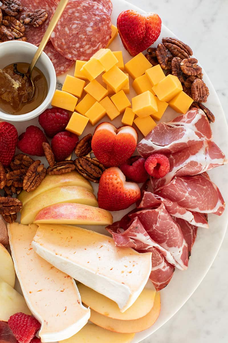 Meat and cheese on a board with heart shaped strawberries