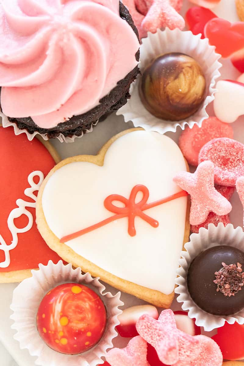 Heart shaped sugar cookies and pretty truffles on a Valentine's Day dessert platter.