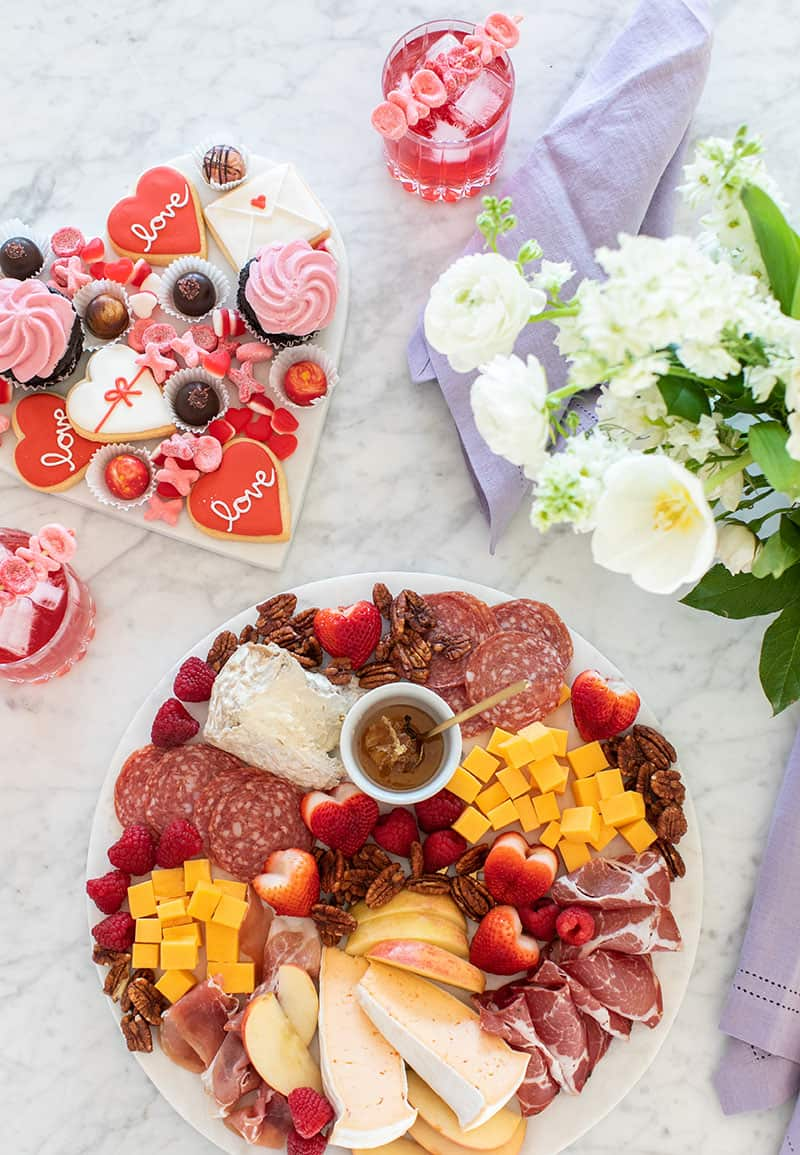 Valentine's Day meat and cheese platter with honey, flowers, desserts and cocktails on a marble table. Dessert platter too.