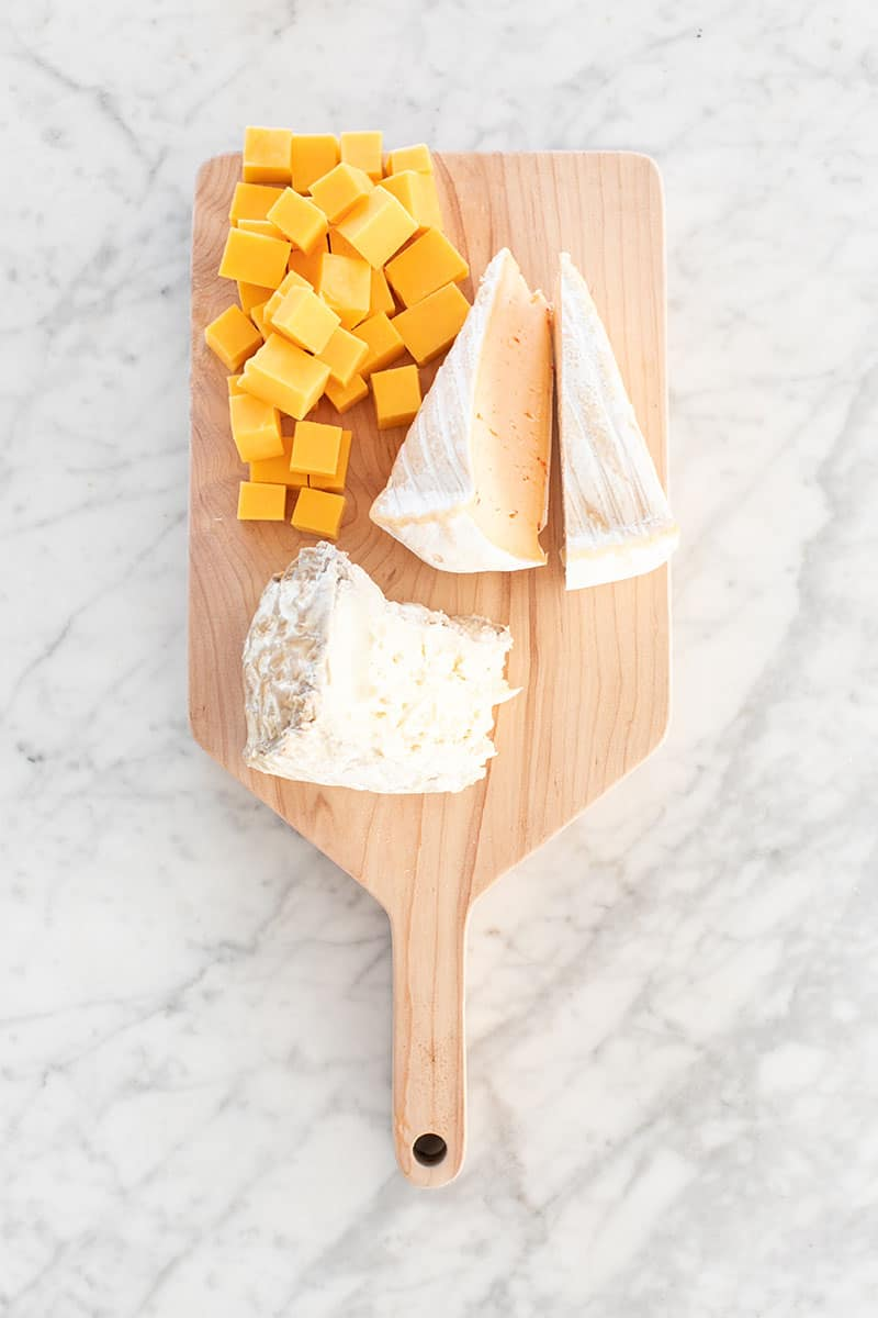 Three types of cheese on a wooden board.