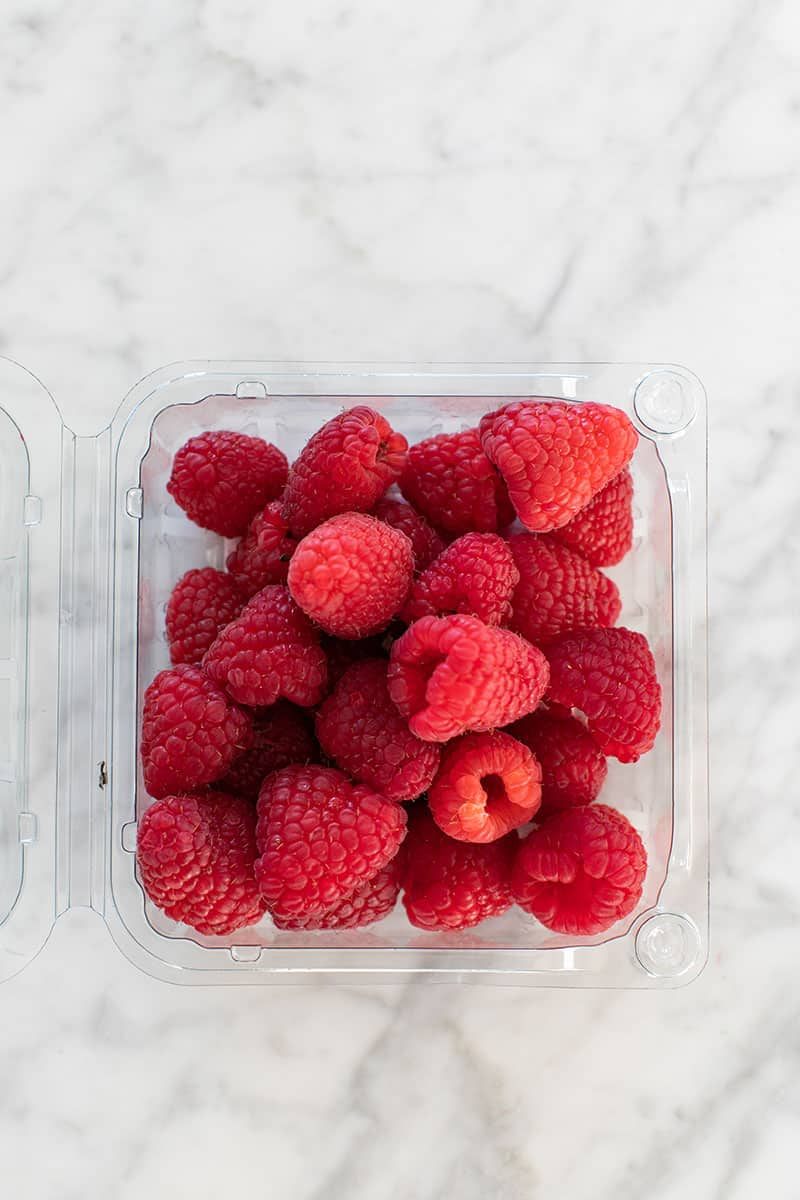 Container of fresh raspberries for dessert platter.