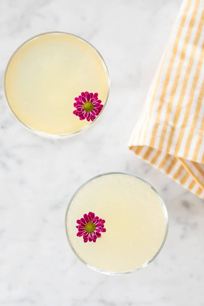 Two bee's knees cocktails with purple flowers and yellow striped towel.