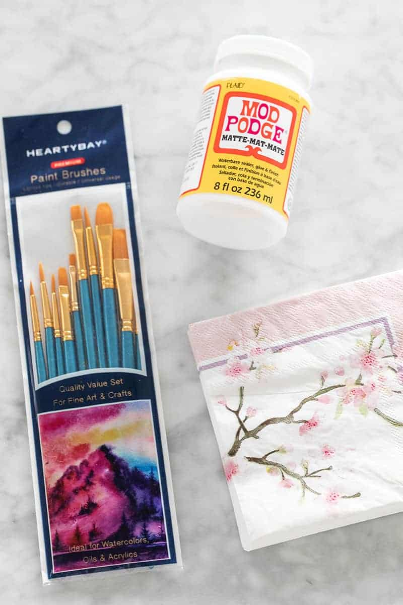 Napkins, mod lodge and paint brushes on a marble table