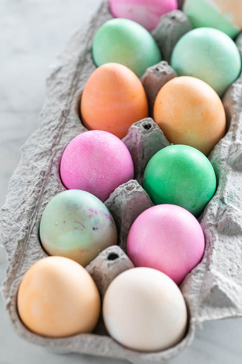 Colored easter eggs in an an egg carton
