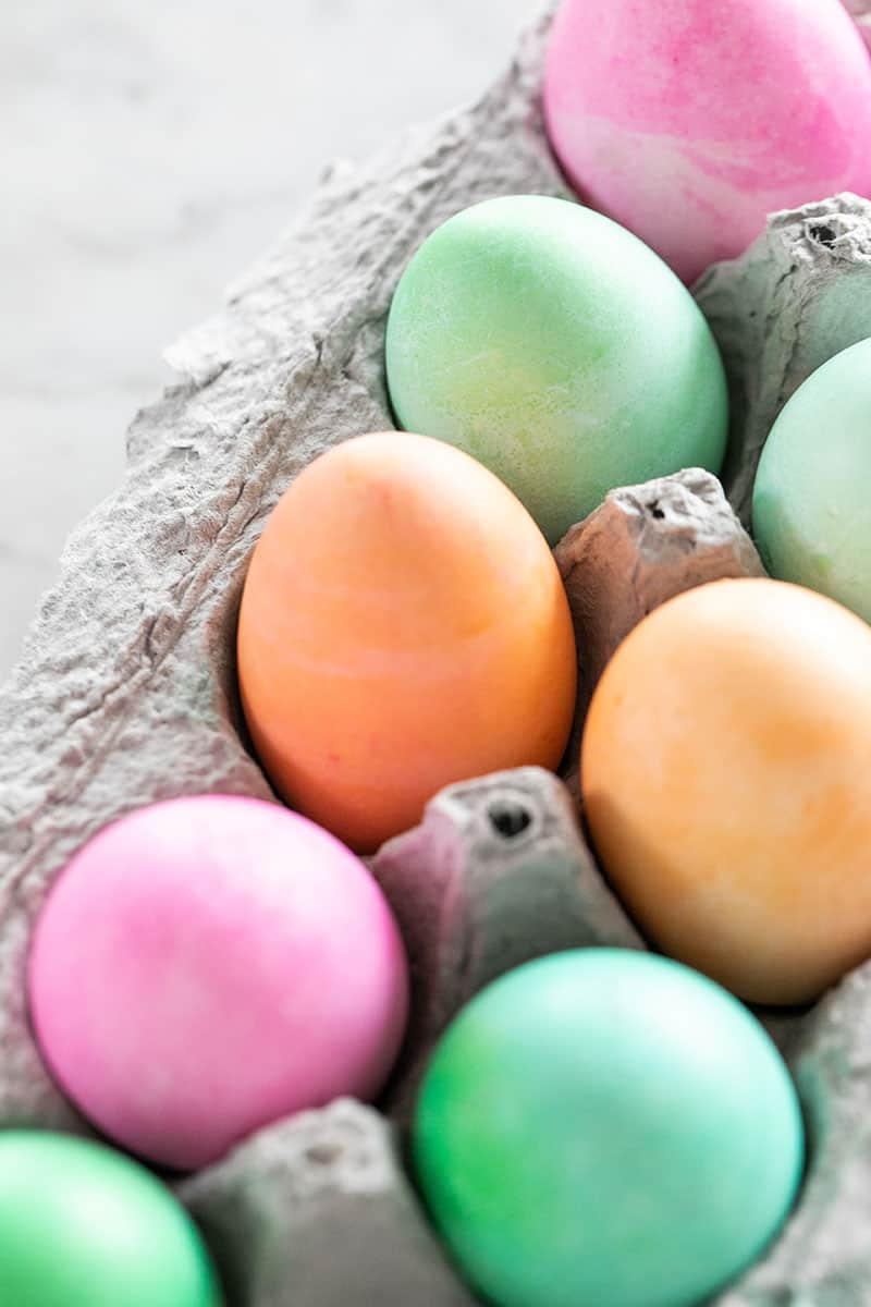 Orange, green and pink dyed Easter eggs in a carton.
