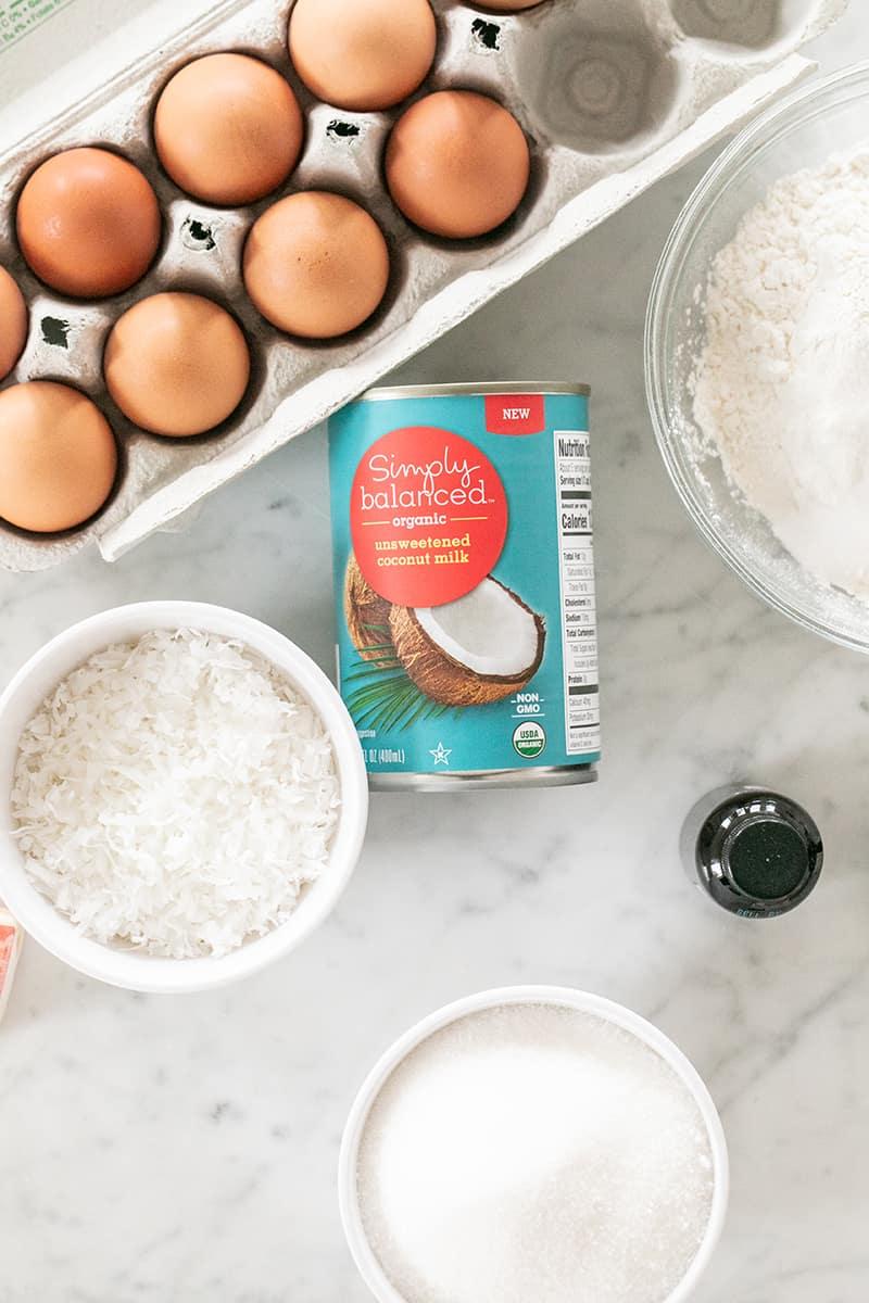 Canned coconut milk, eggs, shredded coconut and flour on a marble table.