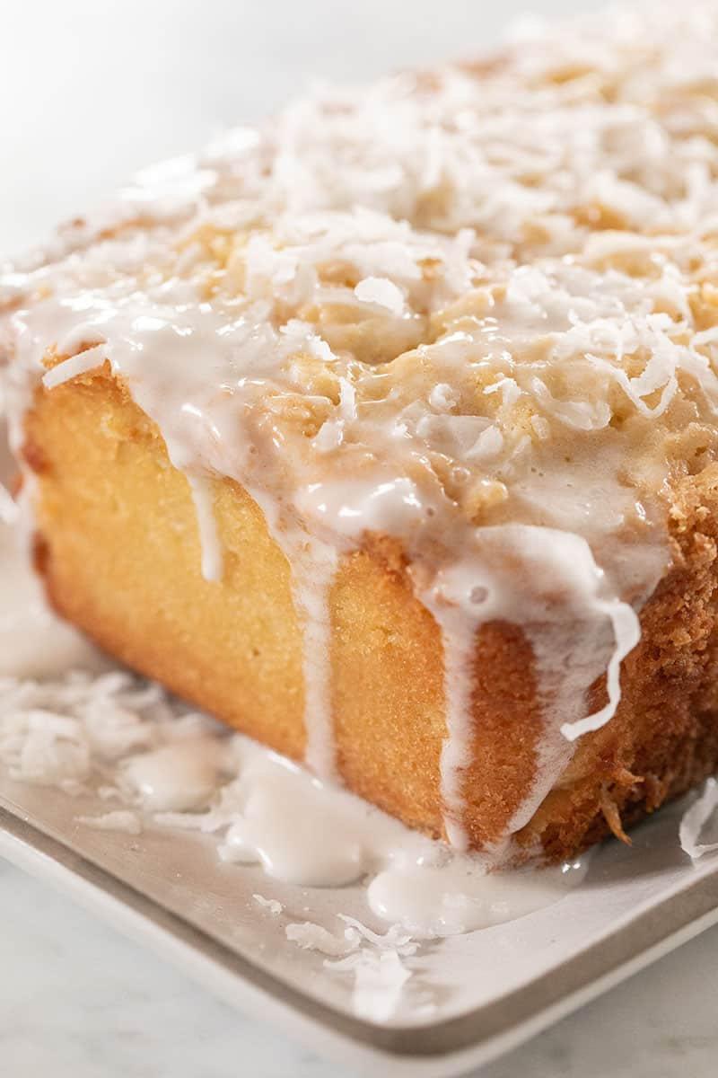 Homemade coconut loaf cake with a coconut glaze and topped with shredded coconut.