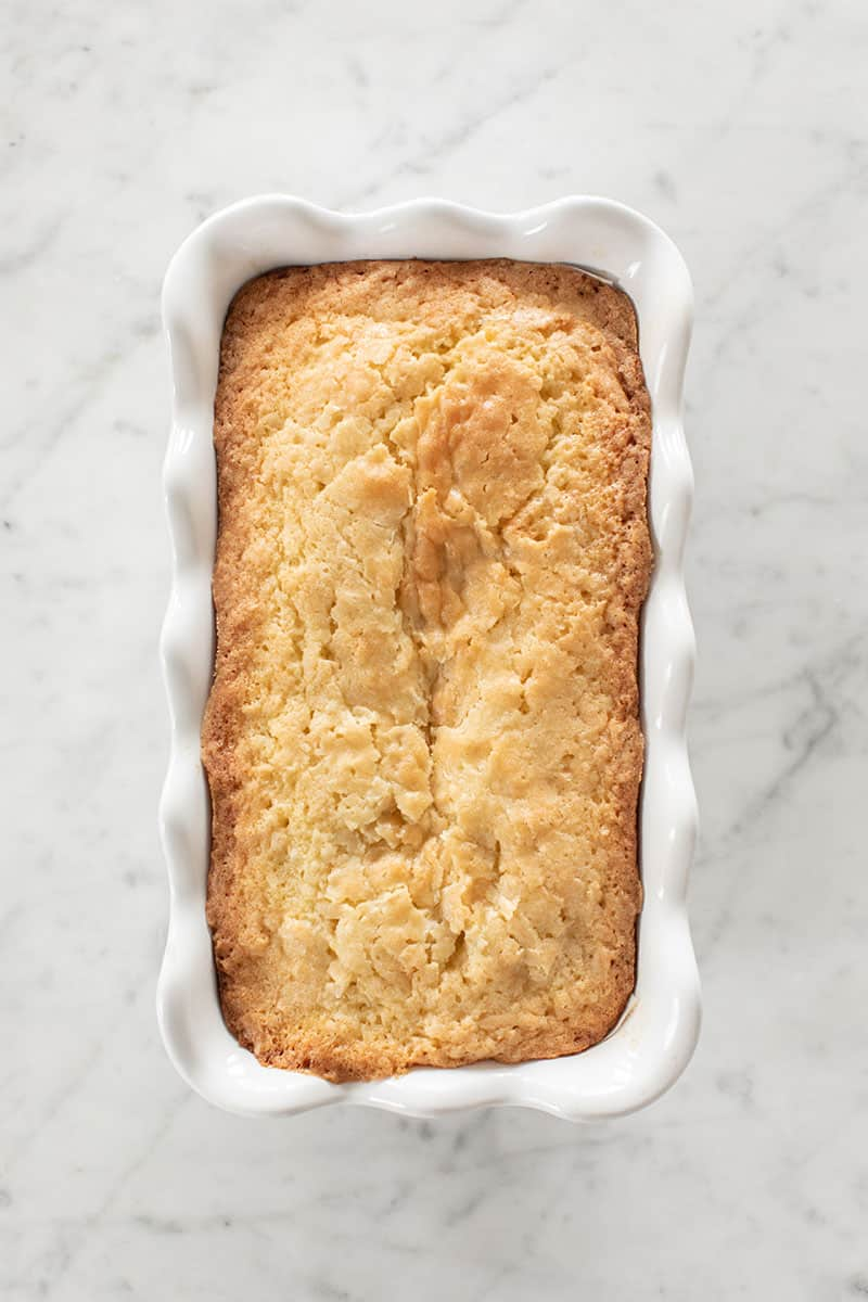 Golden brown coconut loaf cake in a ceramic loaf pan.