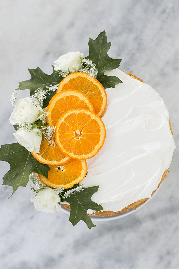 Rum cake with orange slices and flowers over the top.