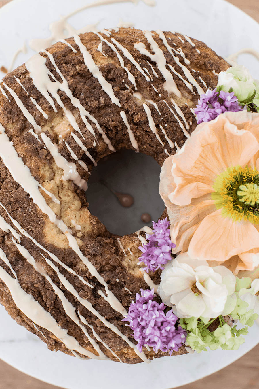 Coffee cake with glaze and garnished with flowers.