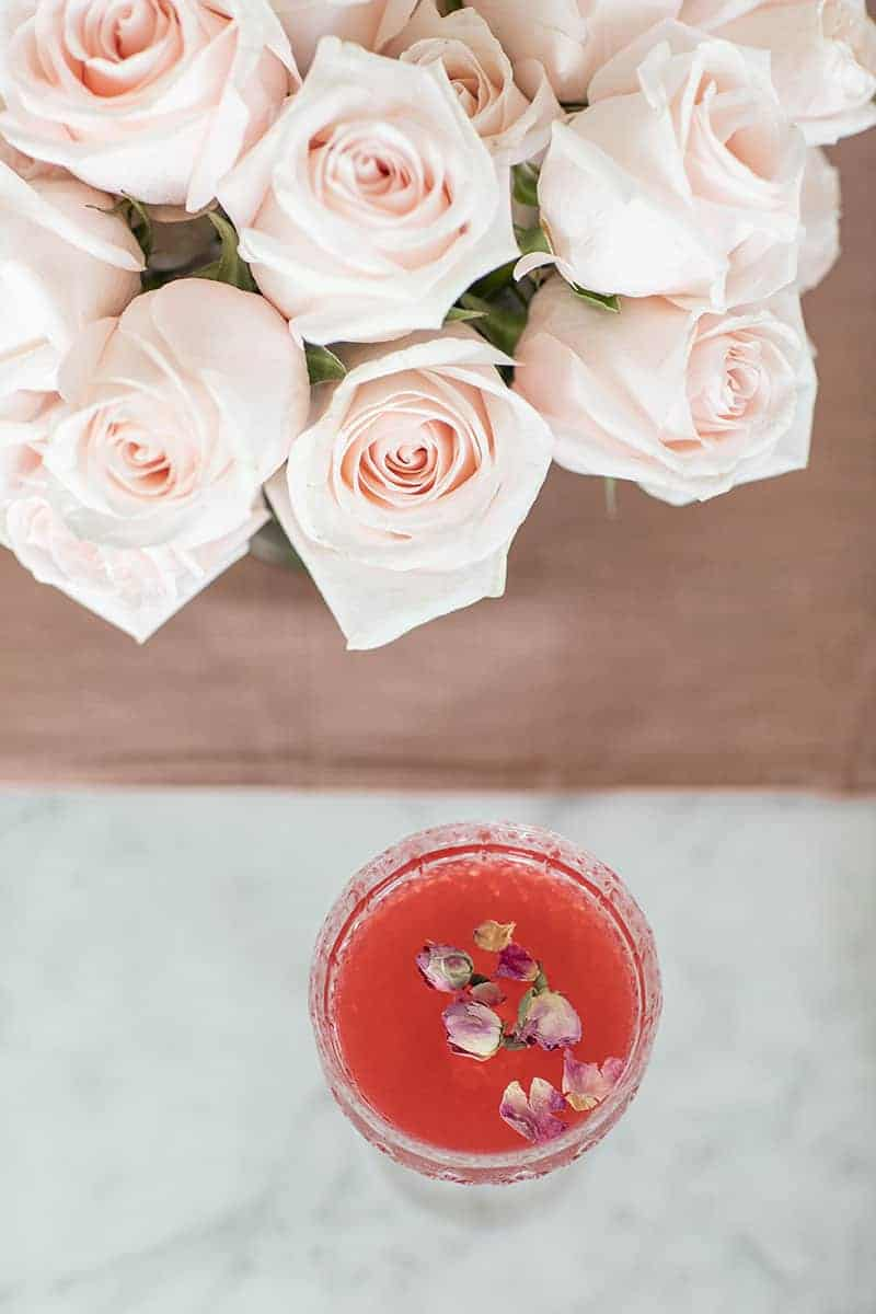 Red cocktail with dried rose petals with pink roses.