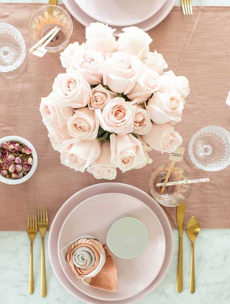 Table setting with pink flowers, pink plate and gold flatware.
