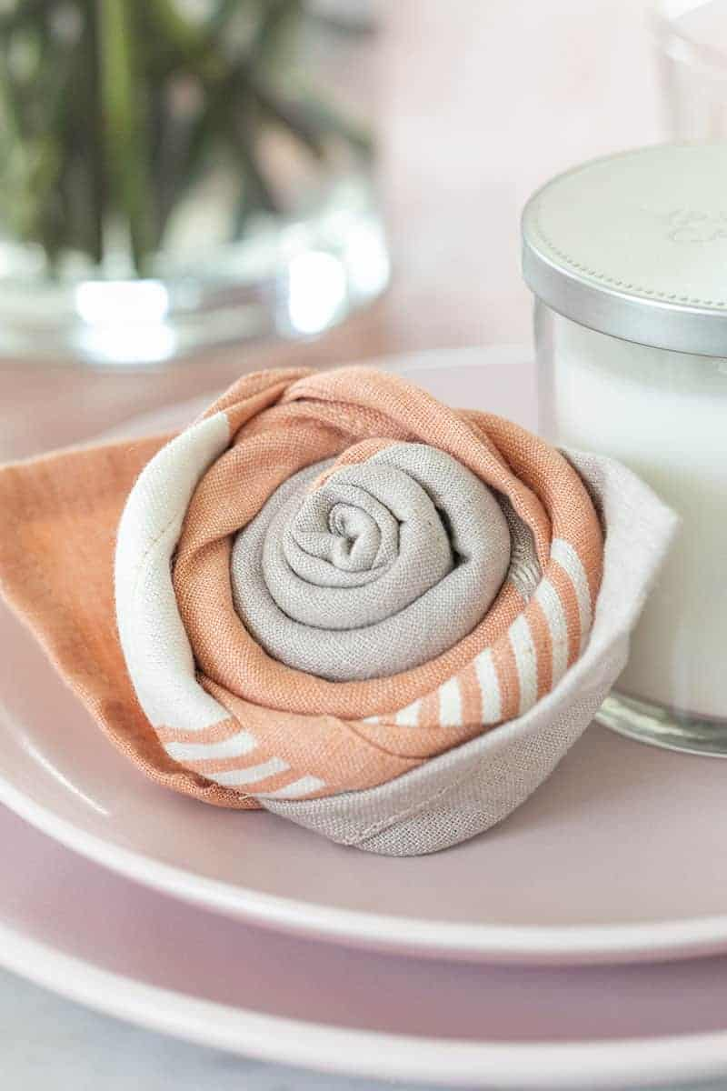 Mother's day napkin fold, a pink rose on a plate.
