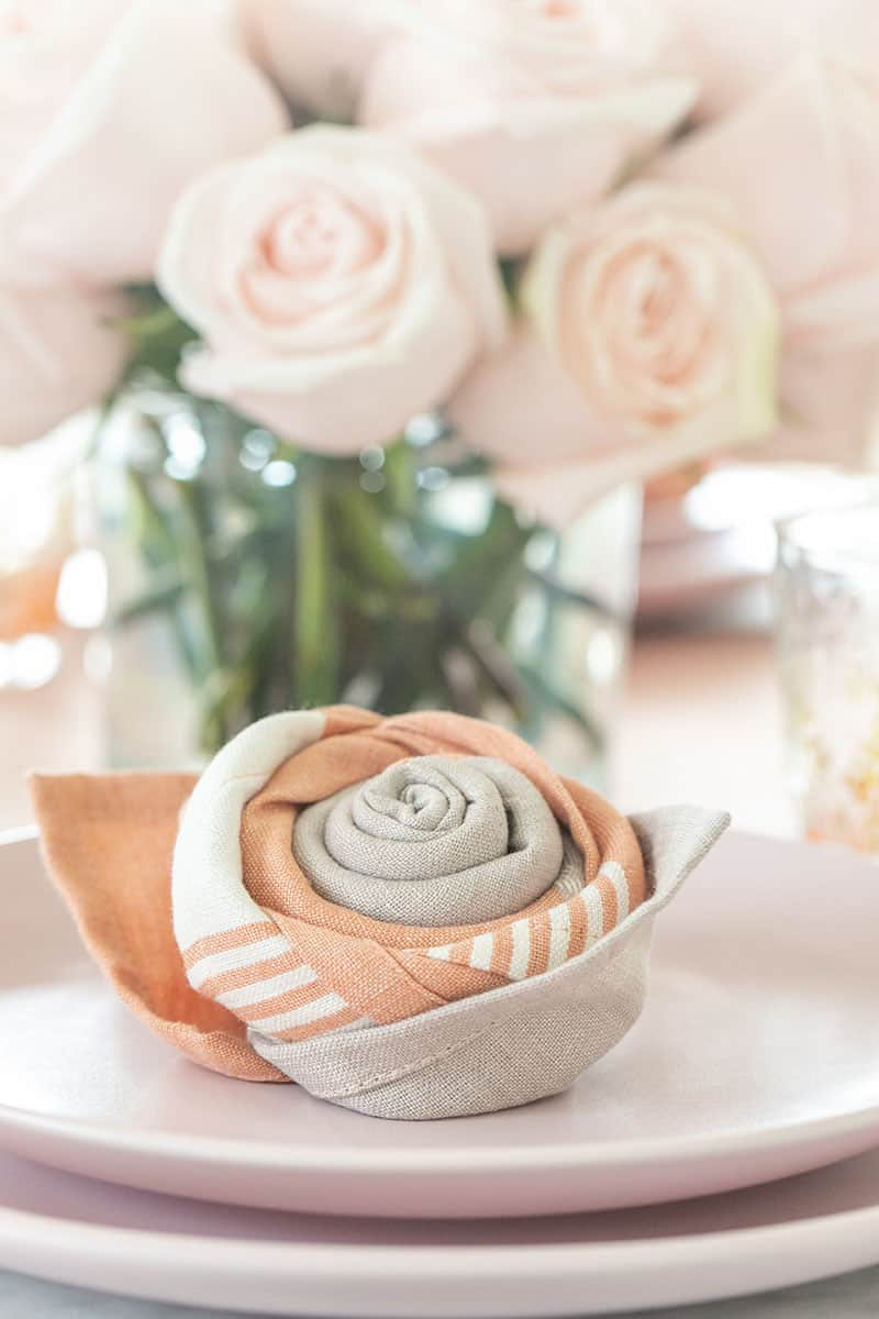 Rose napkin fold on a pink plate with pink roses.