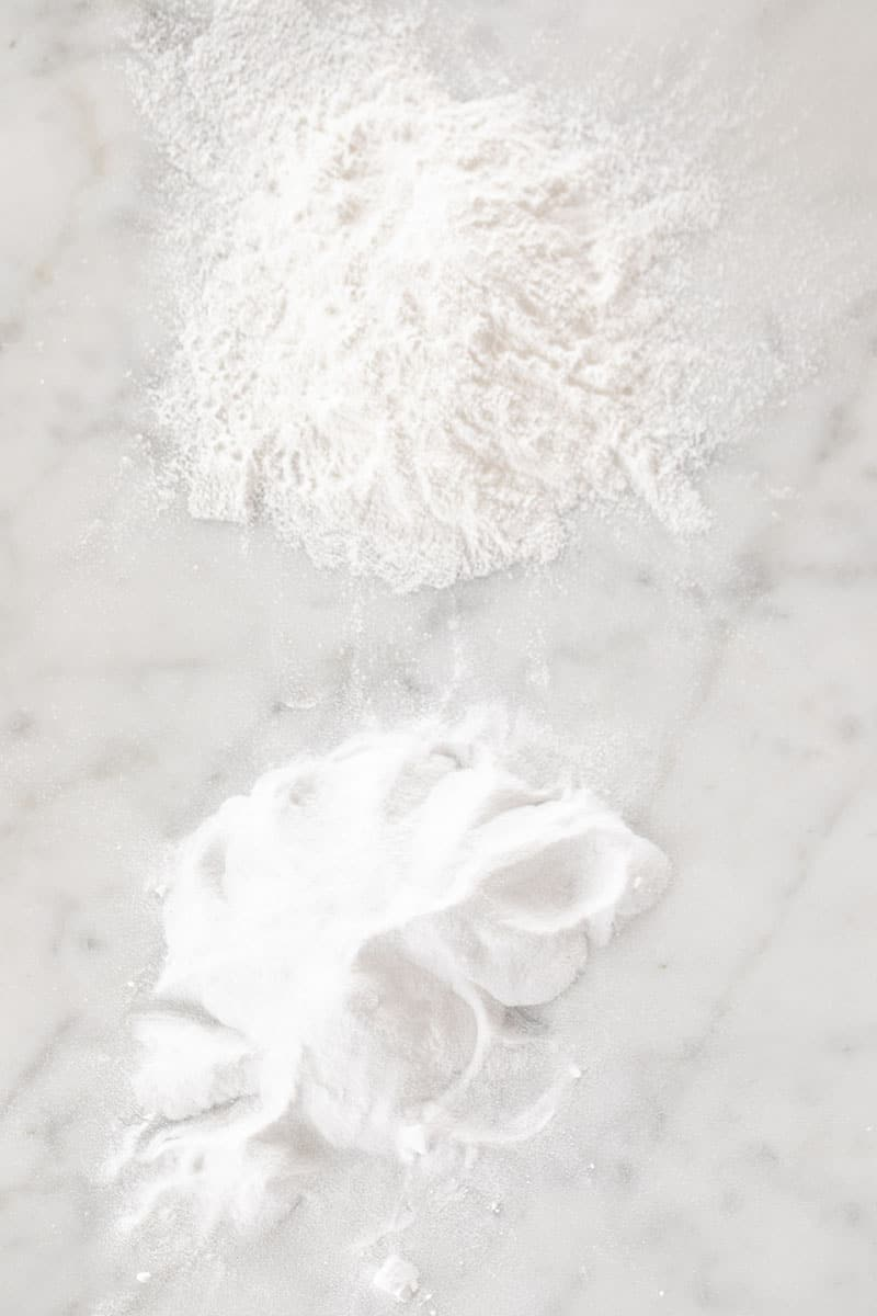 Baking soda and baking powder on a marble table.