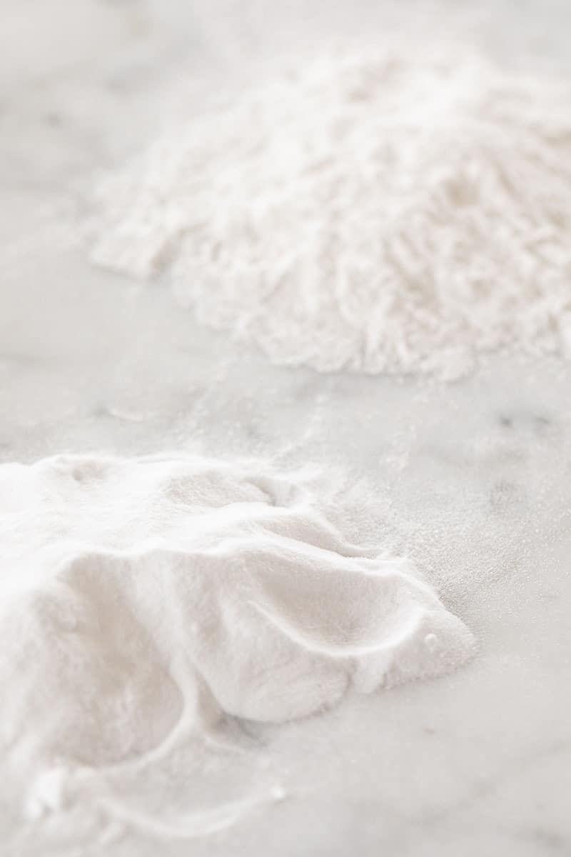 pile of baking soda and baking powder on a marble table.