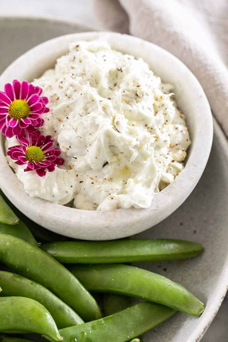 A small bowl filled with blue cheese dip garnished with flowers and a side of peas.